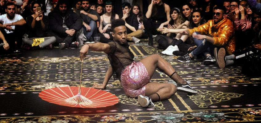 man dancing with umbrella on rug at event
