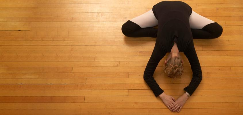 woman in ballet attire stretches on hardwood floor