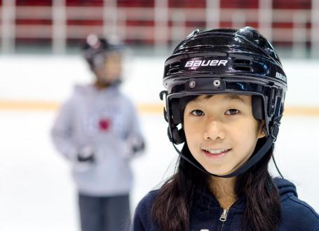 Young Skaters wearing hockey helmets