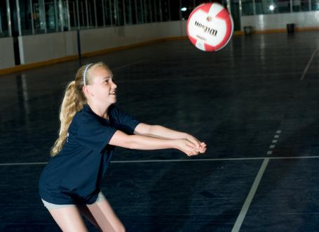 A girl bumps a volleyball