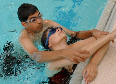 A boy practices life saving techniques in the pool