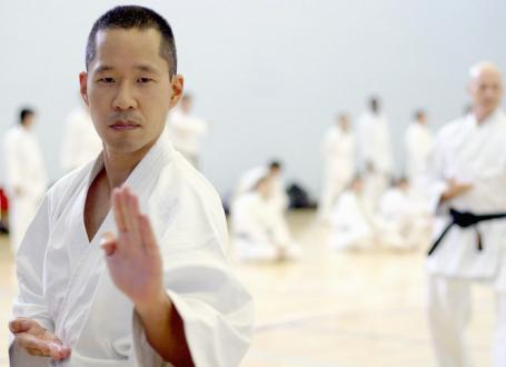 A man in knife-hand pose in Karate Class